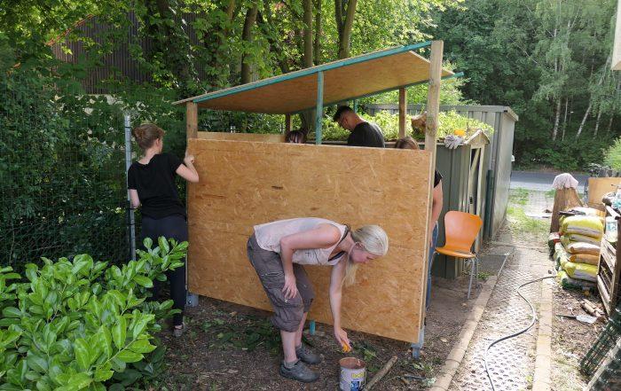 Teameinsatz Garten Mitarbeiter streichen Fahrradschuppen